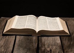Holy bible open on rustic wooden table in dark night.
