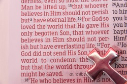 Holy Bible opened in John 3:16 with a cross reflecting the color red. Close-up. Horizontal shot.