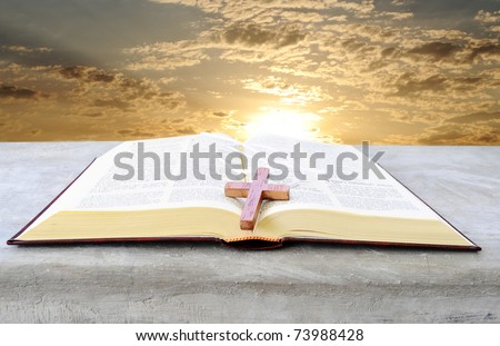 Holy bible over a pulpit with a bright sunrise as background