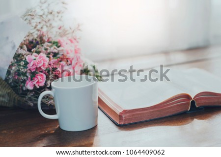 Holy bible with a cup of coffee and flowers on wooden table against window light, Christian background with copy space