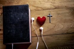 holy Bible with headphone and silver cross on wooden table ,read and listen to the voice of God, symbol of christian concept.