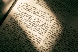 Holy Bible with light casting on Genesis