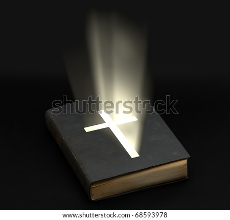 Holy bible with shining cross over black background