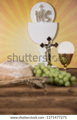 Holy communion a golden chalice with grapes and bread wafers #1371477275