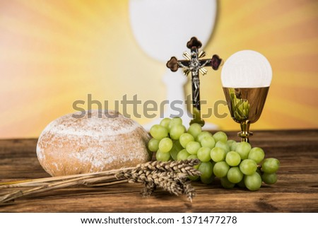 Holy communion a golden chalice with grapes and bread wafers #1371477278