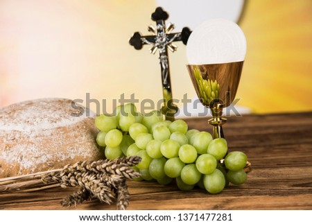Holy communion a golden chalice with grapes and bread wafers #1371477281