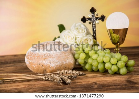 Holy communion a golden chalice with grapes and bread wafers #1371477290