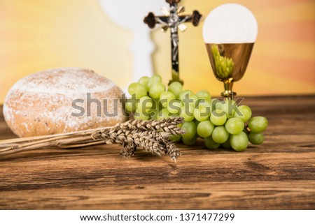 Holy communion a golden chalice with grapes and bread wafers #1371477299