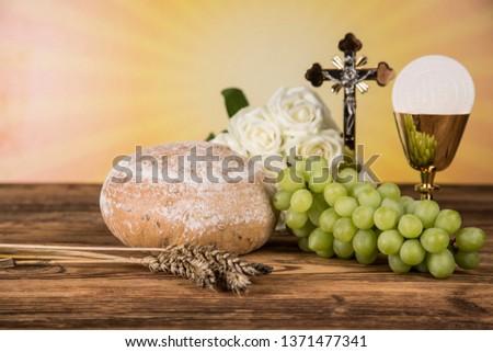 Holy communion a golden chalice with grapes and bread wafers #1371477341