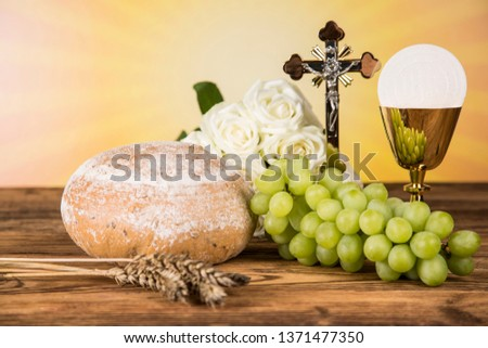 Holy communion a golden chalice with grapes and bread wafers #1371477350