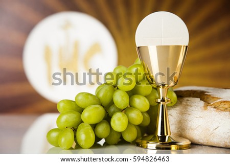 Holy communion a golden chalice with grapes and bread wafers #594826463