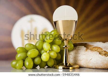 Holy communion a golden chalice with grapes and bread wafers #594831446