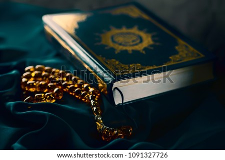 Holy islamic book Koran on the draped table with an amber rosary. Ramadan Kareem beautiful poster, banner, postcard for the celebration of the festival of the Muslim community #1091327726