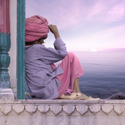 Holy man meditating near Ganges in India.