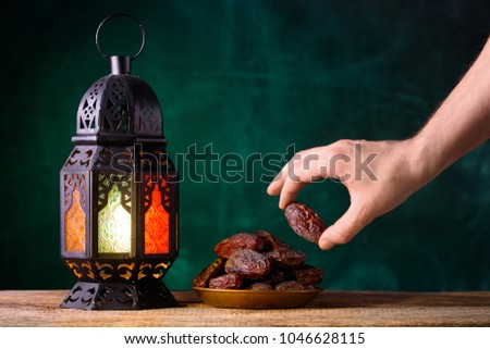 Holy month of Ramadan concept. Righteous Muslim Lifestyle. Fasting. Ramadan lantern, dates. A man's hand reaches out to a plate with dates on a wooden table. Dark green background.