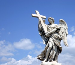 Holy statue of carved winged angel with cross in blue sky and clouds