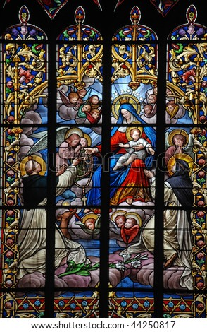 holy virgin Mary and Jesus receive a rosary from a saint on stained glass window in brittany - stock photo