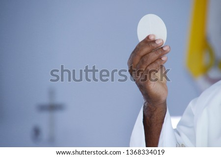 Holy Wafer. Holy communion in church. Taking holy Communion. Priest celebrate mass at the church. Cup of glass with red wine, bread. Feast of Corpus Christi. #1368334019