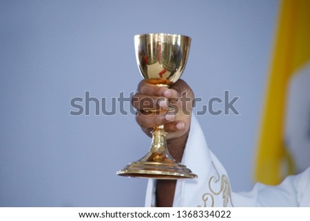 Holy Wafer. Holy communion in church. Taking holy Communion. Priest celebrate mass at the church. Cup of glass with red wine, bread. Feast of Corpus Christi. #1368334022