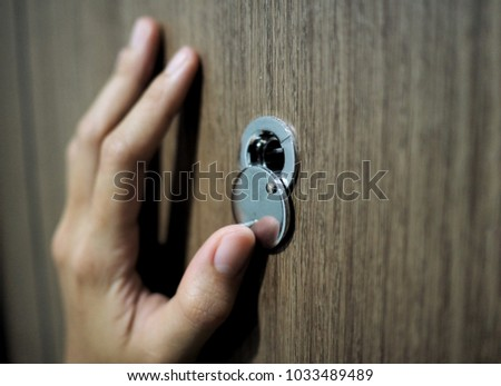 Home alone woman watching on peephole door when somebody knocking at the door.