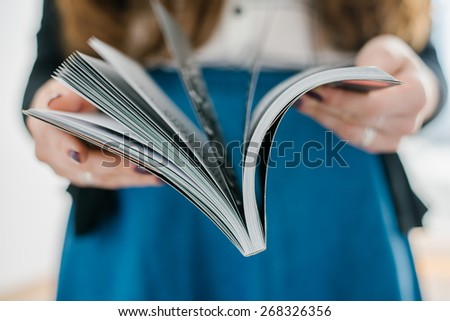 home and leasure concept - smiling woman reading magazine at home