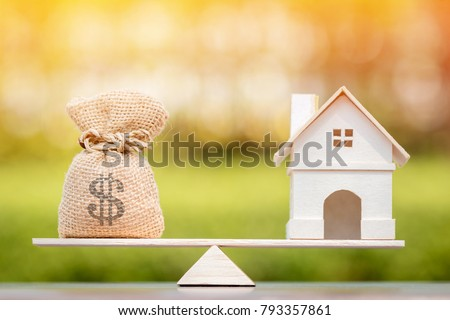 Home and money bag put on the scales with balance put on the wood in the public park, Saving for buy a new house or real estate and loan for plan business investment in the future concept.