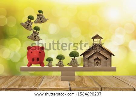 home and piggy bank,growing tree on top put on scales with balance,bokeh nature background,concept money saving,investments,financial planning in bank,for buying house and investing in real estate