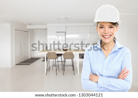 Home architect business woman house inspection of new condo project building inspecting remodeled modern kitchen. Happy Asian architect professional with hard hat helmet.