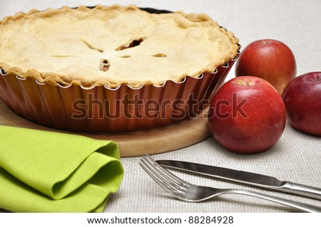 Home-baked apple pie, straight from the oven. Vintage enamel pie plate, fork and knife.