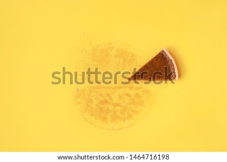 Home baked slice of pumpkin pie on a yellow background and the grease traces of the whole pie. Eaten sweet pie concept. Above view of traditional pie. #1464716198