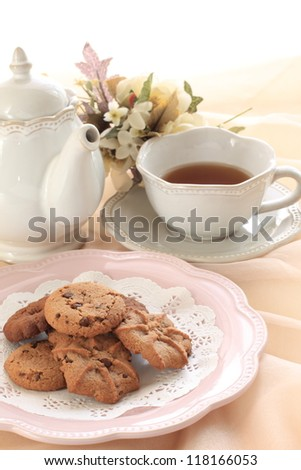 home bakery of chocolate chips cookie on elegant pink dish with English tea