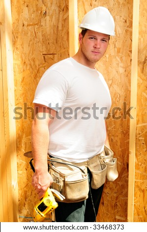 Home Builder Wearing A Hard Hat And Holding A Power Drill