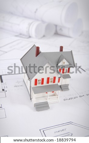 Home building concept shot with blueprints and small home model