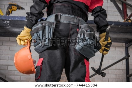 Home Building Contractor Preparing For the Job. Safety Helmet in Left Hand and Hammer in the Right. #744415384
