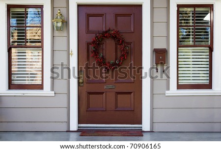 Home burgundy door with wreath with two white trimmed blinded windows