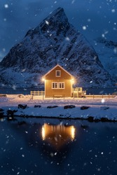 Home, cabin or house at night, Norwegian fishing village in Reine City, Lofoten islands, Nordland county, Norway, Europe. White snowy mountain hills, nature landscape background in winter season.