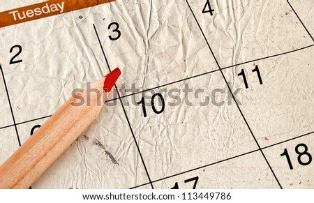 home calendar with dates and red sharpened pencil