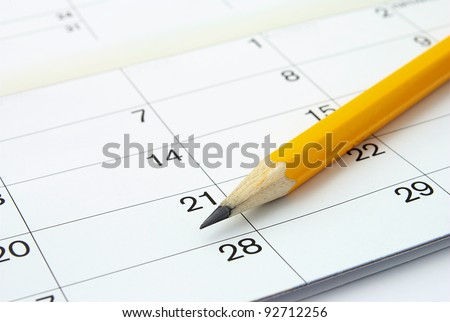 home calendar with dates and yellow sharpened pencil