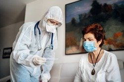 Home care doctor wearing personal protective equipment(PPE).Infection and cross-contamination during home visit to suspect COVID-19 senior patient.Checking temperature with termomether.Fever symptoms