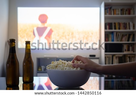 Photo of  Home cinema entertainment: watching a film from a video projector in a room. Dim living room with a cinematic picture projected on the wall, human hand grabbing popcorn