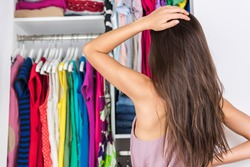 Home closet indecision woman choosing her fashion outfit on clothing rack. Shopping spring cleaning concept. Morning woman having too many clothes thinking of what to wear in organized clean walk-in.