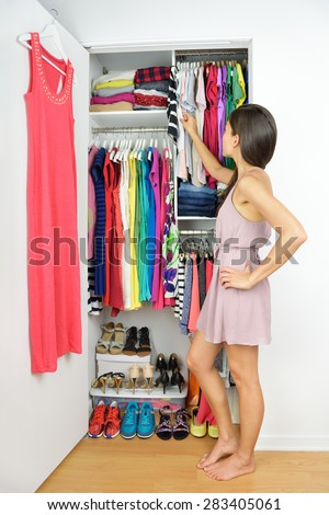 Home closet - woman choosing her fashion clothing. Shopping concept. Woman having many new clothes facing indecision in front of many choices of stylish dresses and skirts in organized clean walk-in.