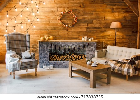 Home comfort. Armchair near the fireplace with firewood. Photo of interior of room with a wooden wall, wreath and garlands, Christmas atmosphere #717838735