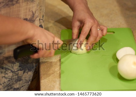Home cooking concept. Woman cuts onions on a green cutting board. Close up. Focus on hand and cutted onion