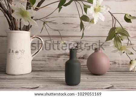 Home cozy corner: two empty ceramic vases of grey and pink colors and a white metal vase with flower in bloom at wooden background #1029051169
