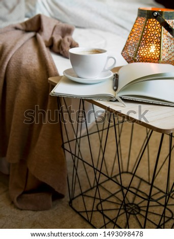 Home deco indoor with candle holder and notebook on coffee table, cozy blanket,cozy winter interior details #1493098478