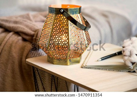 Home deco indoor with candle holder and notebook on the table, cozy blanket,cozy winter interior details  #1470911354