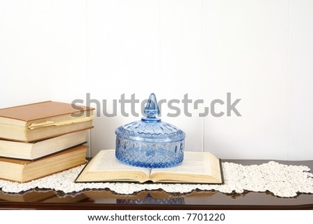 Home decor arrangement with books, crystal dish, silk flowers and antique doily.