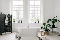 Home decor ideas in contemporary bathroom design. Empty freestanding bathtub against large windows, wooden folding screen and green house plants on floor. Concept of classic bath in modern apartment