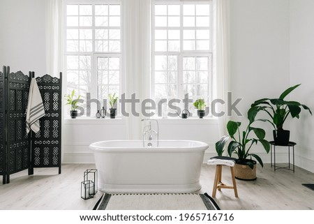 Home decor ideas in contemporary bathroom design. Empty freestanding bathtub against large windows, wooden folding screen and green house plants on floor. Concept of classic bath in modern apartment Foto d'archivio ©